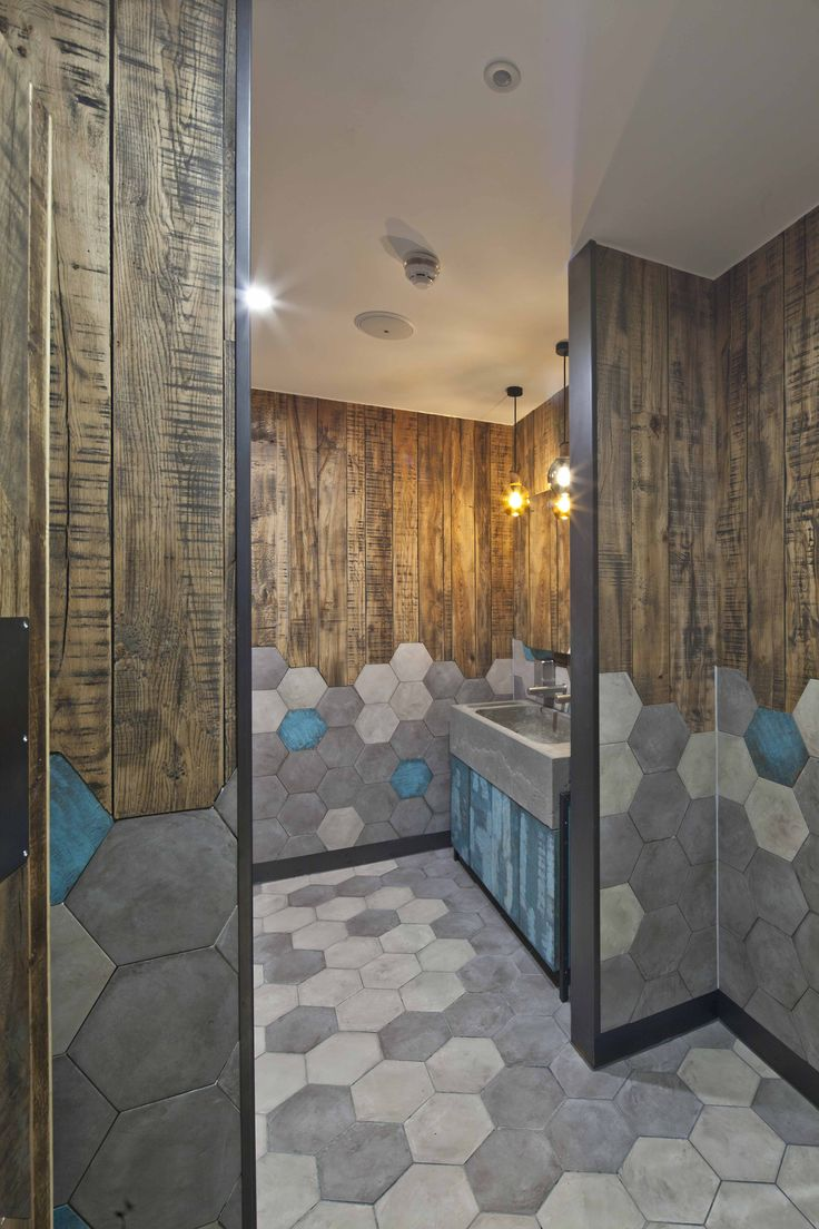 Cool grey hexagon tiles paired with wood in this very hipster bathroom design. Industrial lighting and exposed wood.
