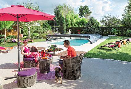 Salon de jardin au bord de piscine. bain de soleils roses devant l'abri de piscine
