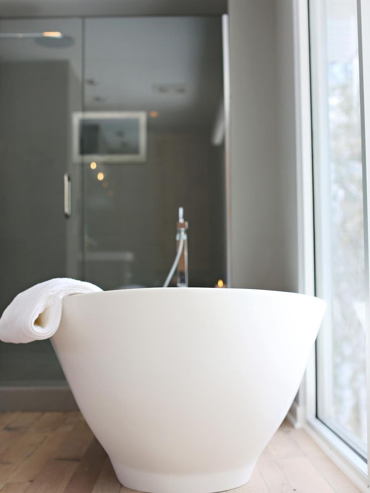 A modern freestanding tub provides a soothing experience while watching TV.