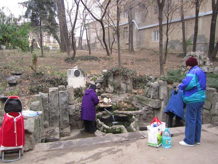 """População local buscando e bebendo água no Parque Cismigiu, em Bucareste, Romênia. O parque tem lago, jardins, café e bancos, e uma """"fonte"""" de água. Esta fonte, desde há muito, era local no qual as pessoas buscavam a água para abastecer suas casas, pois acreditavam que era a mais pura da região. O município testou a água e verificou que era impura. Fecharam a fonte. A reclamação foi grande, então a """"fonte'' foi reaberta, mas a água agora é encanada, a mesma de todas as torneiras da cidade."""