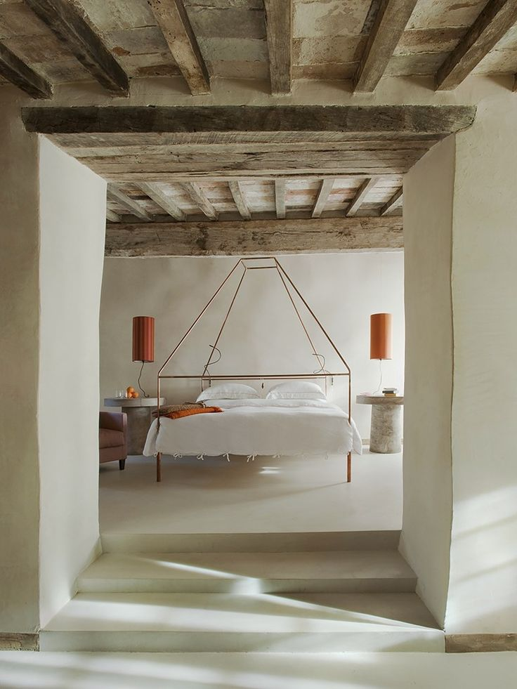 Natural white walls, empty floors, copper bed frame + table lamps