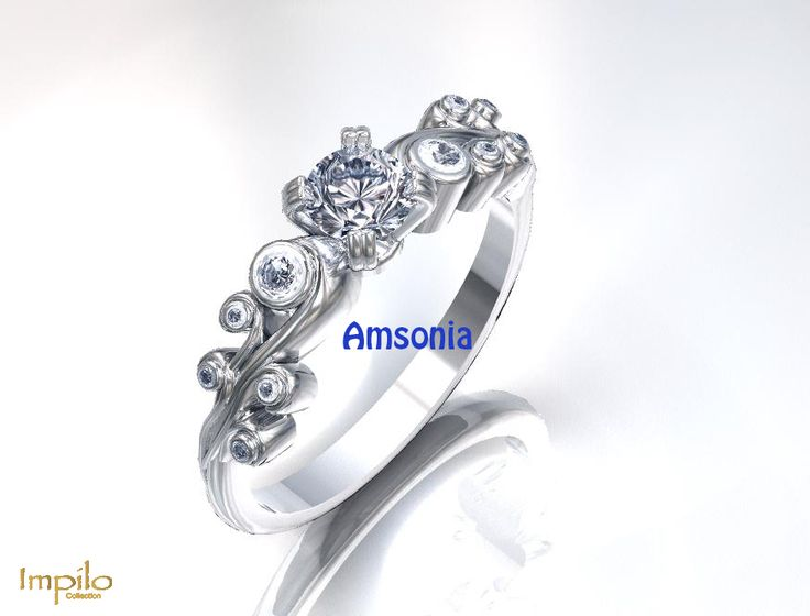 """""""Amsonia"""" - Round brilliant cut diamond with small diamonds on each band in a floral pattern."""