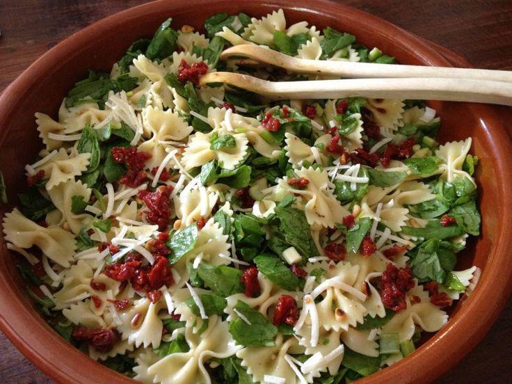 Pastasalade Met Spinazie recept; pasta (500 gr), lente uitjes (ca. 6 stuks), potje zongedroogde tomaatjes, pijnboompitjes, zak verse spinazie, oregano, honing-mosterd dressing, parmezaanse kaas