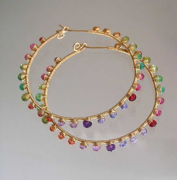 .....unique...exotic....full of color! Hand wrought 20 gauge 14k gold filled hoop earrings are studded with a riot of colorful gemstones. Deep tangerine sapphires, vesuvianite, peridot, tsavorite, emerald, rubellite tourmaline, pink tourmaline, ruby, red spinel, tanzanite, and amethyst. MADE TO ORDER WITH A TWO WEEK TURANAROUND. Slight gemstone variations. Four photo displays back. Finished length is 2 1/8. Width is 2 1/4. thank you~ tracey Lots more bella jewels hoops here::: h...