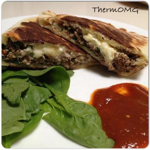 Beef and Feta Gozleme •250g low fat (or non fat) Greek Yoghurt •300g Self Raising Flour •Pinch of Salt •1 brown onion (peeled and halved) •1 clove of garlic •10g oil •½ tsp fennel seeds •1 tsp cumin seeds •½ tsp turmeric •1 tsp salt •500g mince •Feta •Spinach leaves •Grated chedder cheese