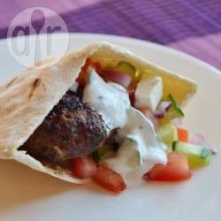 Pitabroodjes gevuld met zelfgemaakte kofta van rundergehakt, een tomaat-komkommersalade en tzatziki. Een heerlijke zomerse maaltijd, lekker bij de barbecue als alternatief voor een broodje hamburger.