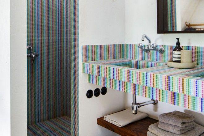 In una delle stanze da bagno a disposizione degli ospiti la proprietaria ha optato per un rivestimento in mosaico colorato per il lavabo e l'ampio box doccia.