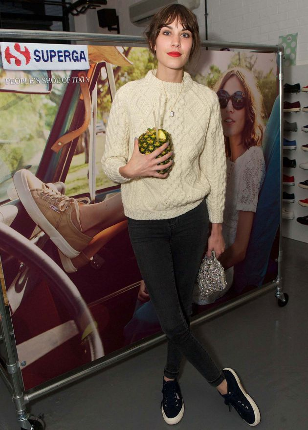 Alexa Chung in a cream cable knit, skinny black denim, Superga sneakers, & a bright lip.