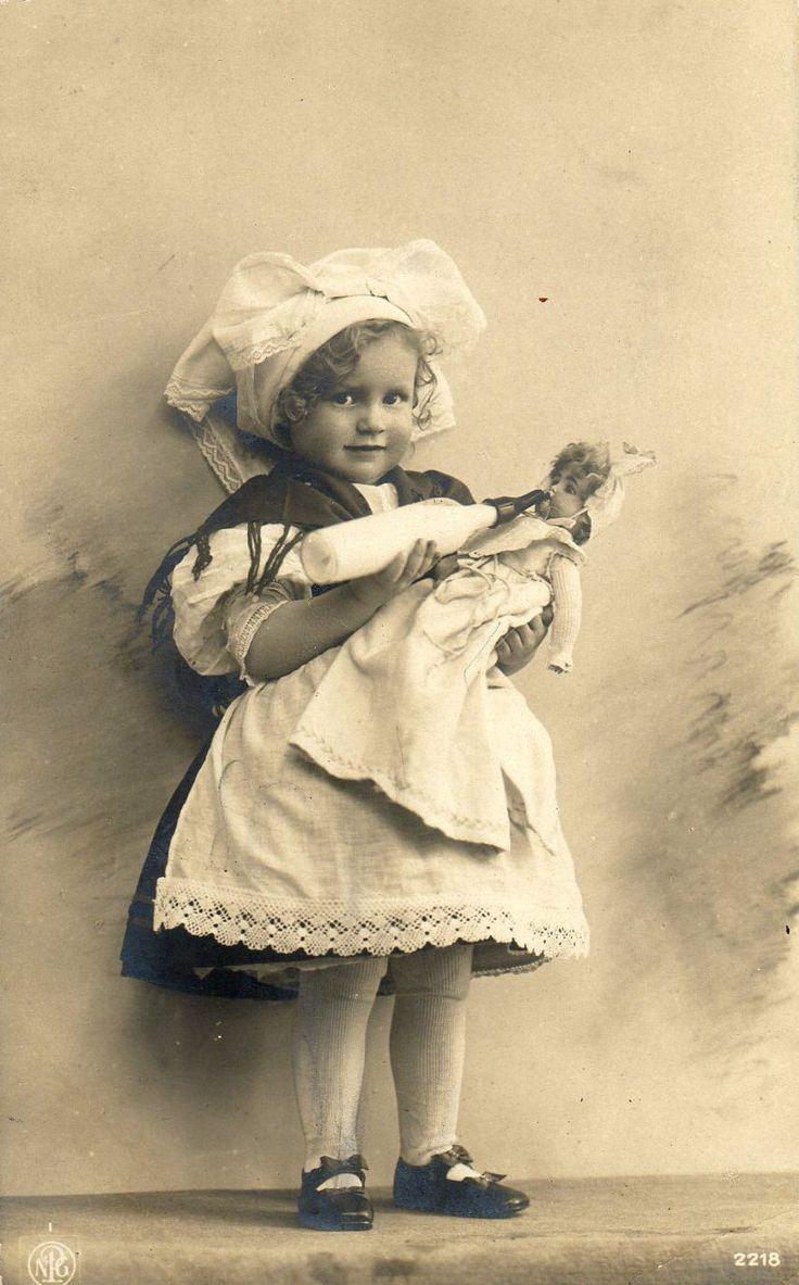Antique photo of little girl feeding her doll a bottle, circa 1900.