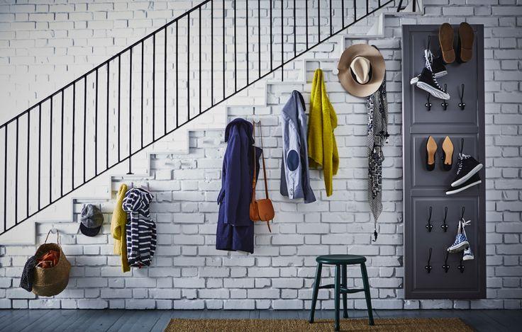 Haken an einer Wand seitlich eines Treppenaufgangs verwahren alles für den Gang vor die Tür. Daneben befindet sich eine BODBYN Tür in Grau, hinter der sich ein Spiegel verbirgt. Und weitere Haken, an denen Schuhe aufbewahrt werden.