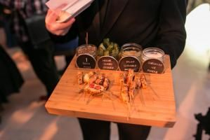 A new spin on a classic carnival snack. Holding wooden boards, servers circulated with artisan corn dogs that were sliced into pieces. Accompanying the skewered snack, little jars held condiments such as house-cured pickles, kraut-caraway mustard, and cheddar ale fondue. Plus, one extra container provided a handy spot for dirty picks.