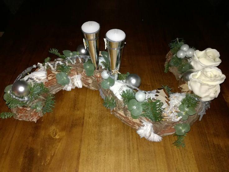 Kerst bloemstuk. krans aan 1 kant doormidden dan draaien en er een s vorm van maken. vervolgens beplakken met stukjes boomschors. en als laatste de wax roozen, waxinelicht houders en groene takjes en kerstdecoratie. 07-12-2016