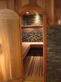 Custom indoor sauna. I like the combination of stone and wood in the sauna.