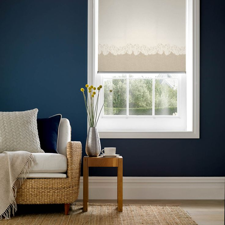 Dramatic navy blue walls enhance the look of the white, cream and biscotti furnishings. Classic roller blinds add an unfussy finish to the room