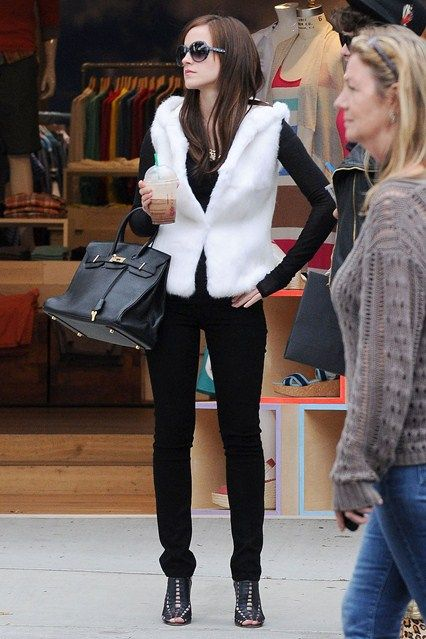 Ema Watson on the set of her new film - The Bling Ring - wearing oversized shades, skinny black trousers and a white gilet.