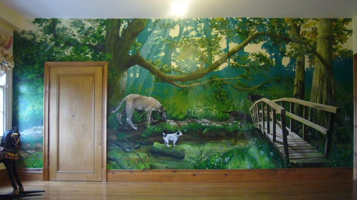 A hand-painted forest mural on a child's bedroom wall, showing detailed family pets, footbridge, trees, and stream with sunbeams through the branches. Mural painted by mural artists One Red Shoe, Neil and Fiona Osborne, England.