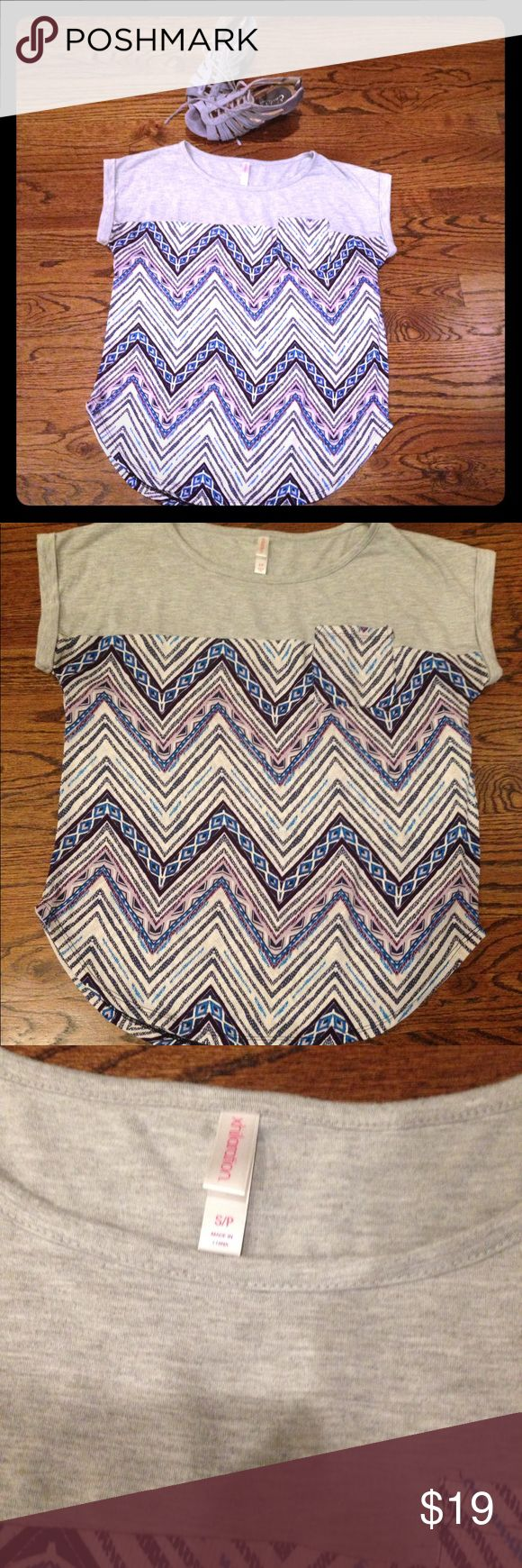 Xhilaration Chevron Pocket Shirt 👚 Trendy blue/lavender/white chevron shirt with front pocket. Sleeves are stitched for a folded look. Upper portion: 65% Polyester/35% Rayon  Lower portion: 💯 % polyester. So comfortable and light weight. Purchased it but it's too small. NWOT Xhilaration Tops Tees - Short Sleeve