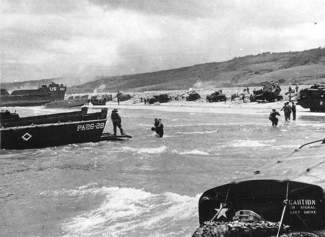 6 juin 1944, mi-journée, secteur OMAHA BEACH devant Le Ruquet, sous le futur cimetière, arrivée de renforts US. Des véhicules sont bloqués sur le banc de galets et ne peuvent le franchir. Au fond à gauche, la vallée de Colleville toujours entre les mains des Allemands.