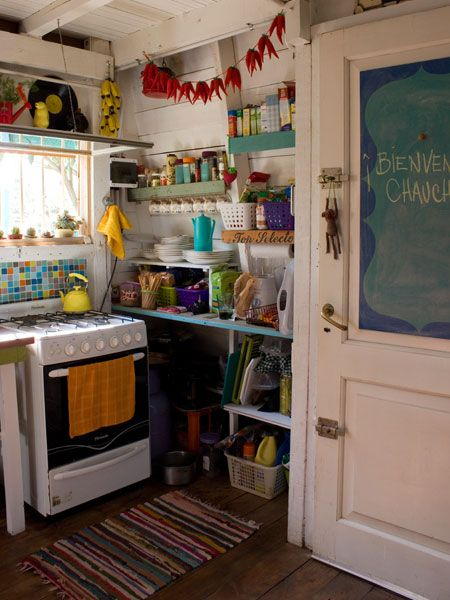 Kitchen. Bright and bohemian. Chalkbboard on the back of door, small colored tiles behind stove
