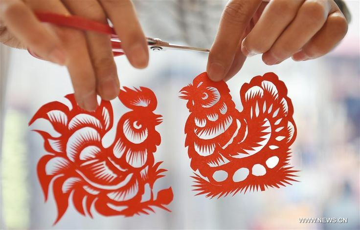 Chang Yangyang, a young folk artist, shows his papercutting works of a rooster and a hen in Mengjin County, central China's Henan Province, Dec. 29, 2016. The Chinese will celebrate the lunar new year, or Spring Festival, on Jan. 28, 2017. Spring Festival this time marks the beginning of the Year of Rooster, according to the Chinese zodiac that assigns one of the 12 animals to each year.