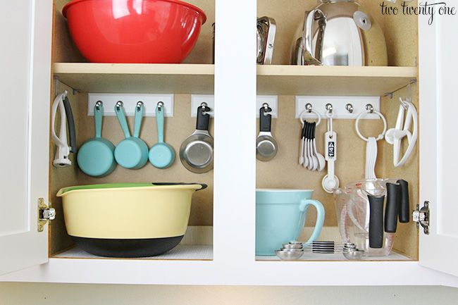 Dedicate a cabinet to organize your baking equipment and take advantage of the vertical space by hanging up your measuring utensils. | via @twotwentyone