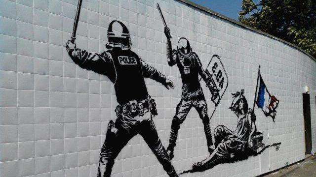 """Sur 6 mètres sur 3, une fresque s'étale, ce vendredi 24 juin, en gare de Grenoble. La peinture met en scène deux policiers armés d'un bouclier """"49.3"""", frappant sur la République. Une fresque qui a particulièrement choqué les policiers. En premier lieu, un représentant syndical."""