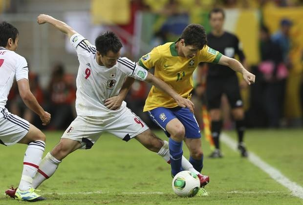 Brazil's Oscar, right, is challenged by Japan's Shinji Okazaki during the opening match between Brazil and Japan in group A of the soccer Confederations Cup at the National Stadium in Brasilia       , Brazil, Saturday, June 15, 2013. (AP Photo/Andre Penner)