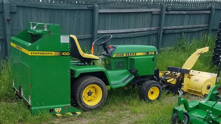 John Deere 318 garden tractor with snow blower and Zamboni 100, in the wild, used to maintain an outdoor skating rink.