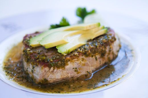 Sushi-grade tuna steaks, pan seared, served with slices of avocado and a ginger, soy, cilantro, lime, garlic sauce.