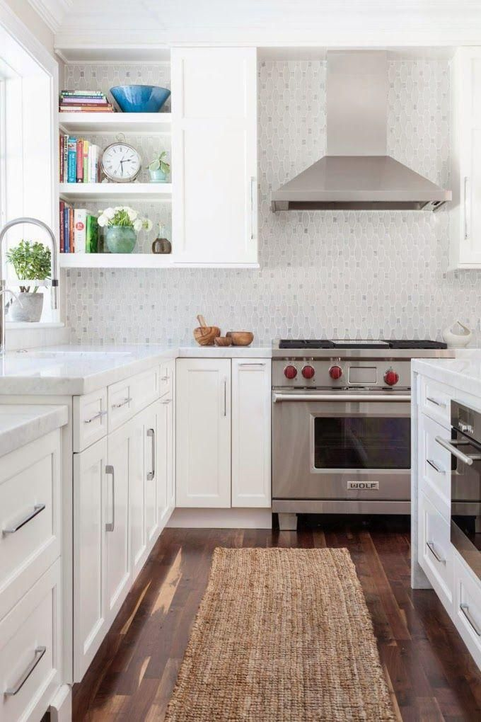 Beautiful white kitchen with a white patterned tile backsplash, dark hardwood floors, classic brushed steel hardware and cabinet pulls, gray and white carrara marble counter tops and a neutral woven jute rug runner in front of the sink.