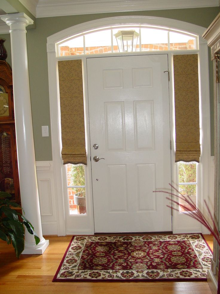 "We do whatever kind of treatments our client asks .. not fond of this look at all.  I know that sidelights are a problem, and I'll show this example as a ""don't"" if a client asks.  Custom roman shades for sidelight windows at front door"