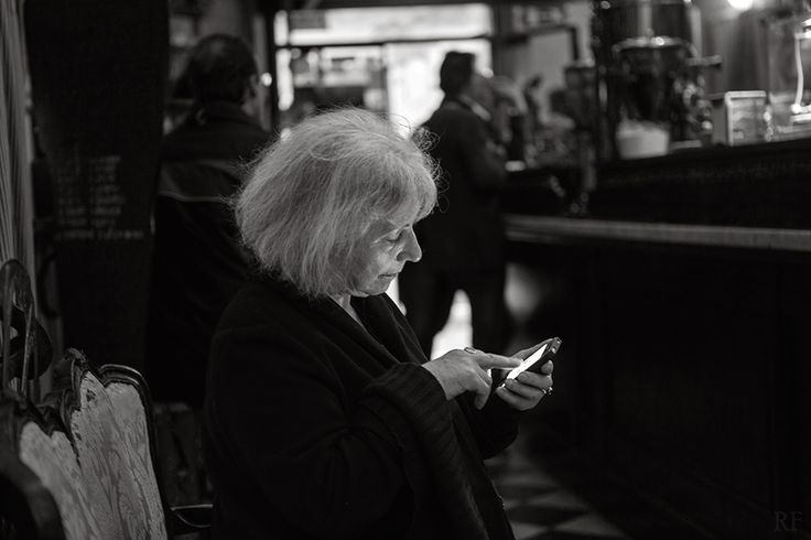 Woman on smartphone in Venice café. By Richard Farland.