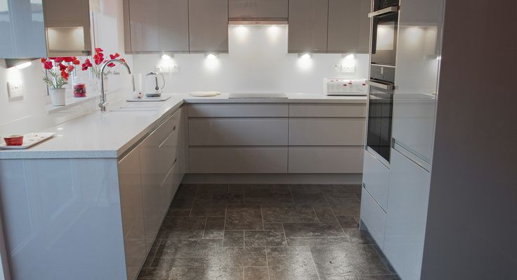 A modern handless gloss grey kitchen by Sheraton with Neff appliances and Corian worktops.