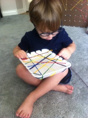 Weaving with a Styrofoam produce tray and some colorful yarn - good use of fine motor skills too.