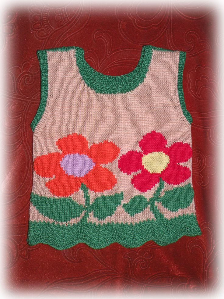 A knitted sleeveless pullover with flowers for a girl