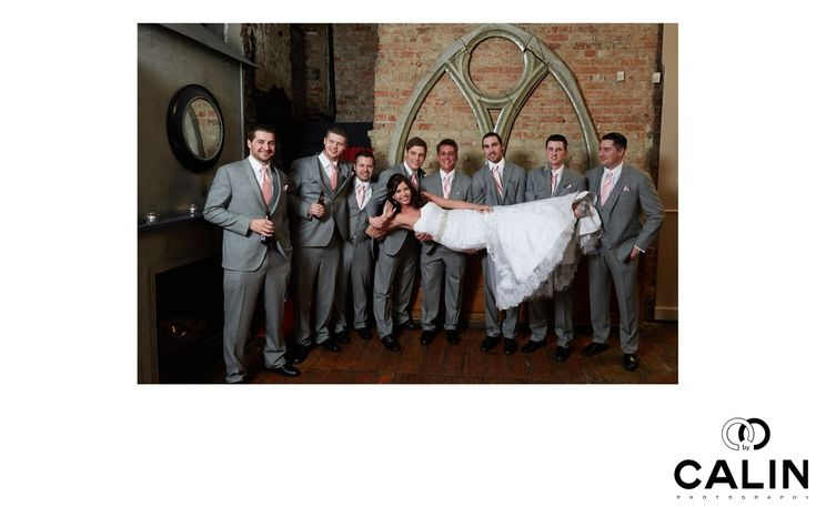 Toronto Wedding Photographer - berkeley-church-wedding-bride-groomsmen: After I captured the moments when the groomsmen&nbsp,threw the groom in the air, it was the bridesmaids turn to suggest something fun.&nbsp,    In this photo, the eight groomsmen surround and support the bride who is placed horizontally in the frame, as if she was leaning in her bed.&nbsp,    Because of the large number of groomsmen, two of them do not hold the bride, but enjoy a beer each, which makes this photo even…