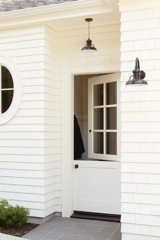 ... Round Window Framed By White Shingle Siding Accented With An Oil Rubbed  Bronze Industrial Style Wall Sconce And Pendant Hung Over A White Dutch Door .