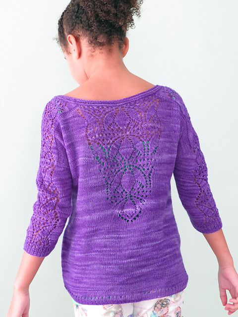 Denne bluse har et smukt hulmønster ned langs ærmerne og på ryggen. Den findes både i en børne- og en voksenudgave og med både korte og lange ærmer.