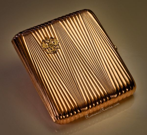 A Russian Imperial Presentation Gold Cigarette Case by FABERGE,  Made in St. Petersburg between 1899 and 1904, workmaster August Hollming. The ribbed rose gold case is decorated with a lemon gold double headed Russian Imperial eagle.