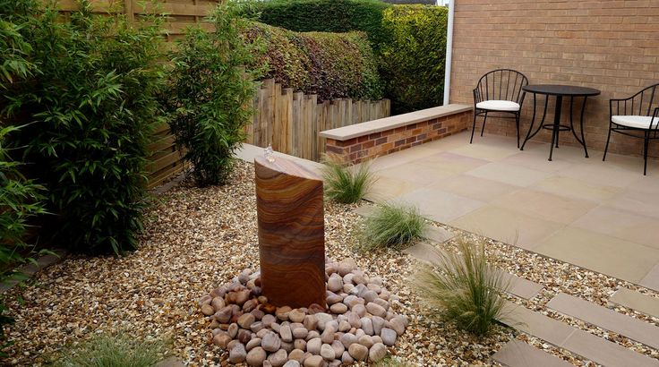 After Redesign & Landscaping - new screens provide privacy, contemporary sawn sandstone planking path set in gravel leads to patio in a sunny area. A stunning contemporary, sculptural rainbow sandstone self-contained water feature adds a 'wow' factor. Sawn sandstone paving, garden screens, grasses, bamboo, contemporary garden, low maintenance garden