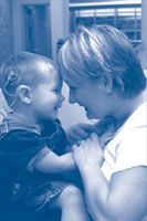 Child with a cochlear implant being held by his mother. Cochlear implants provide a sense of sound to a person who is profoundly deaf or severely hard-of-hearing.