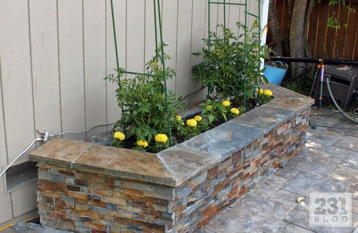 facing-ledger-stone-planter-boxes: Layered Stone Facade Planter Box    If you want a more polished look, building a stone or stone facade planter box can add instant curb appeal to any home. An inexpensive and easy way to spruce up the front or back of your home!