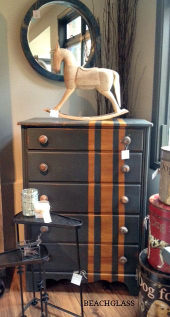 Highboys dresser with dark paint and natural wood stripes.