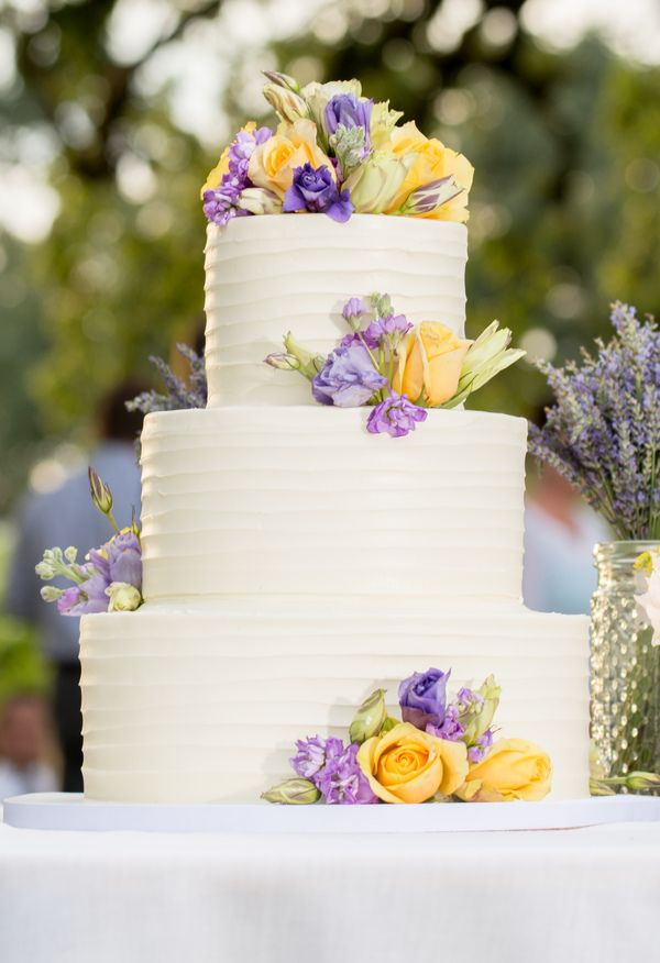 Three-tier cake accented with yellow and purple florals // JSL Pictures