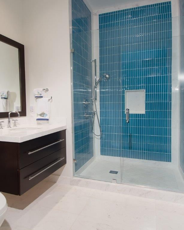 white himalaya marble floors and counter top blue glass tile shower walls