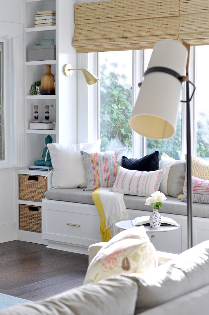 Window Seat and Built-Ins in the living room with drawers, baskets, shelves, and brass sconces