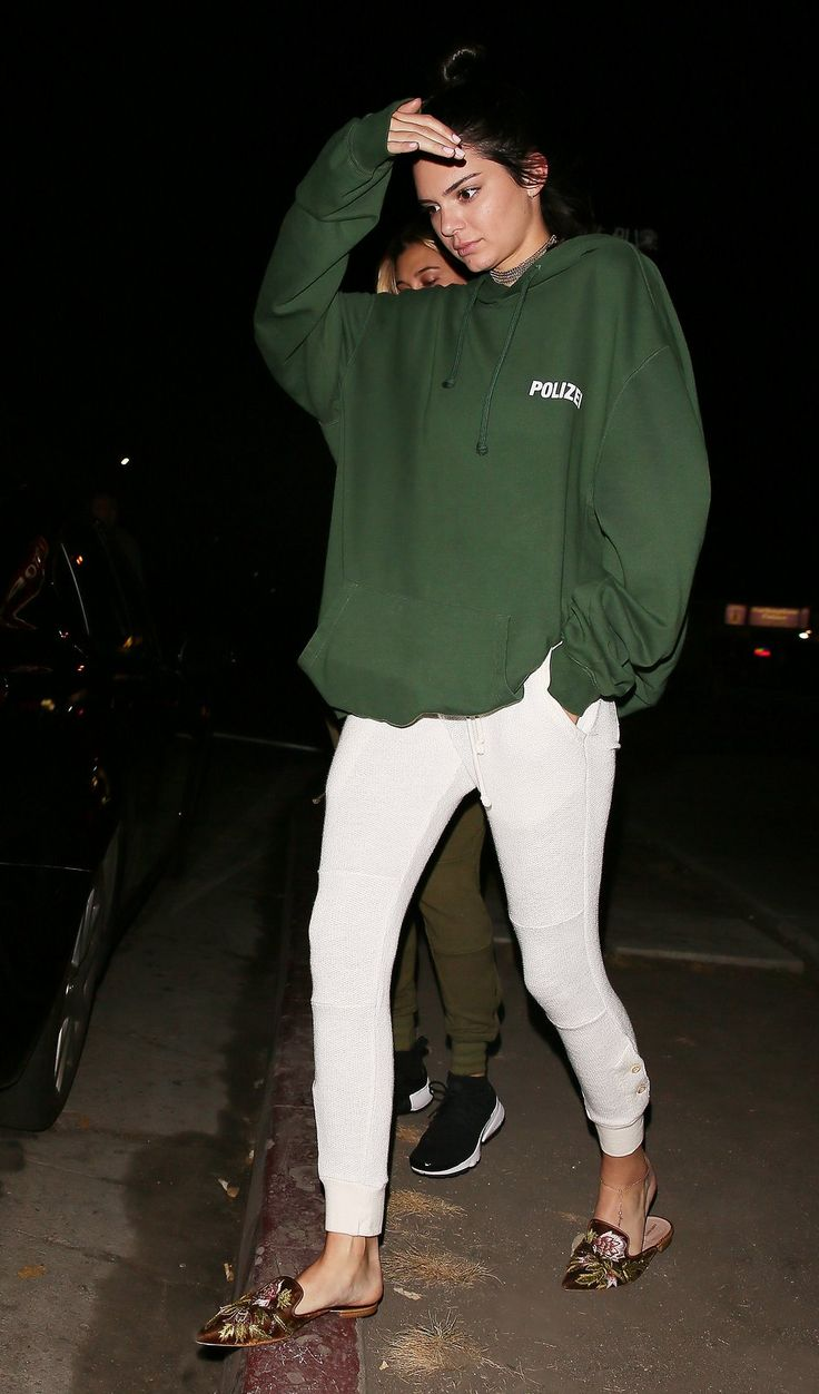 Kendall Jenner in green Vetements hoodie, Lili Claspe choker, white Shadow Hill trousers, and Alberta Ferretti slides.