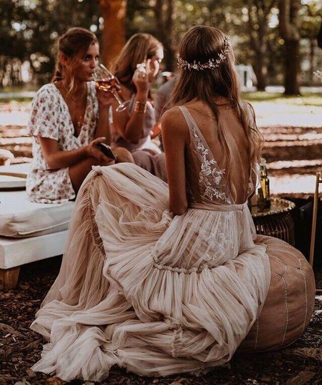 böhmische Braut sitzt draußen auf dem Bodenkissen, Boho-Hochzeitsempfang, Boho Weddi