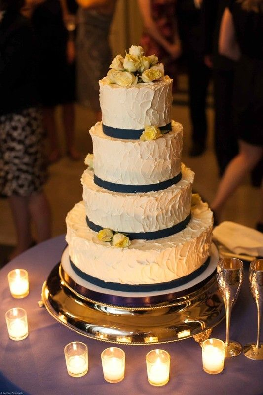 Yellow and navy blue wedding cake idea - tall, four-tier wedding cake with textured frosting, navy blue ribbon + light yellow roses {Fluffy Thoughts Cakes}