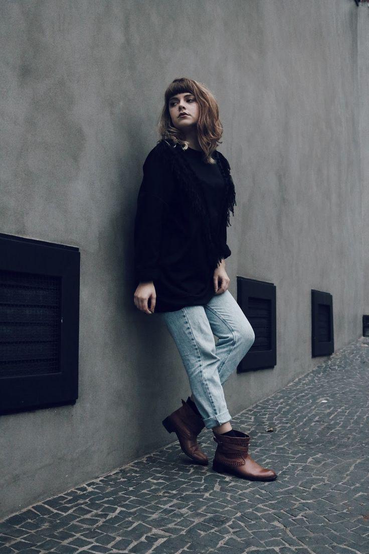 Uma mistura de poesia e moda. Look de inverno com pegada folk, casaco de tricot, calça mom jeans vintage, bota marrom e moletom preto com franjas. loo